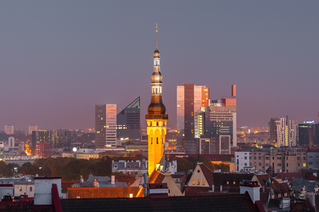 urban scene: Night aerial cityscape with old town hall spire and modern office buildings skyscrapers in the background in Tallinn, Estonia