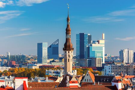 cityscape: Aerial cityscape with old town hall spire and modern office buildings skyscrapers in the background in Tallinn in the day, Estonia