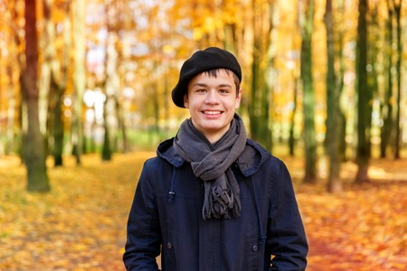 parka: Happy smiling teenage boy in a beret and jacket in the autumn sunny park