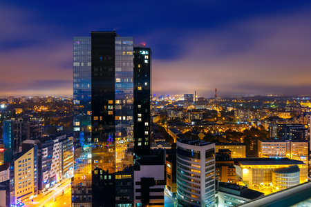 Aerial cityscape of modern business financial district with tall skyscraper buildings illuminated at night, Tallinn, Estonia