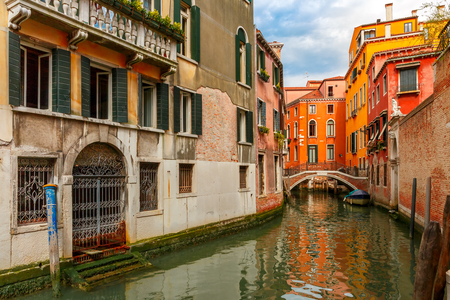 docked: Colorful narrow lateral canal and pedestrian bridge in Venice with docked boats, Italy