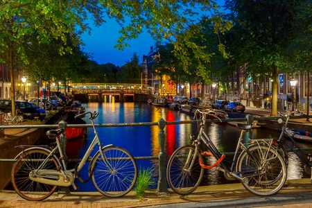 holland: Night city view of Amsterdam canal and bridge, boats and bicycles, Holland, Netherlands.