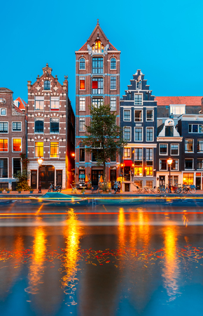 Night city view of Amsterdam canal Herengracht with typical dutch houses and luminous track from the boat, Holland, Netherlands.