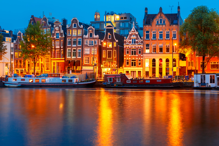 gables: Night city view of Amsterdam canal, typical dutch houses and boats, Holland, Netherlands.