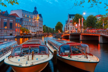 house gables: Night city view of Amsterdam canal, bridge, typical dutch houses and boats, Holland, Netherlands.