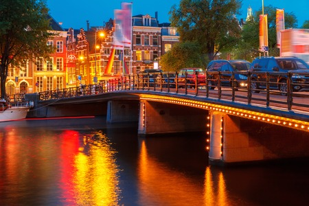 house gables: Night city view of Amsterdam canal, typical dutch houses and bridge, Holland, Netherlands.