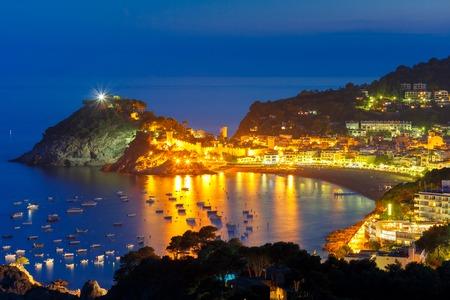 Night aerial view of fortress and fishing boats, Gran Platja beach and Badia de Tossa bay in Tossa de Mar on Costa Brava, Catalunya, Spain Stock Photo
