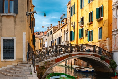 pedestrian bridge: Colorful narrow lateral canal and pedestrian bridge in Venice with docked boats, Italy