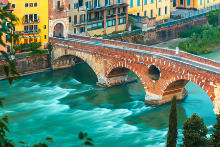 river view: Ancient Roman bridge Ponte Pietra and the River Adige at evening, view from Piazzale Castel San Pietro, Verona, Italy