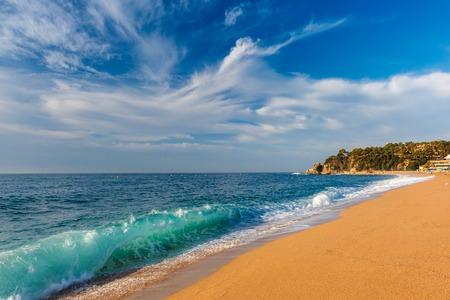 Sea waves and sand main beach at popular holiday resort Lloret de Mar on Costa Brava in the morning , Catalunya, Spain Stock Photo