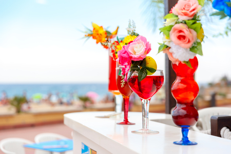 Multi-colored cocktails in high stemware, decorated with flowers and fruit at the bar counter on the beach background. Shallow depth of field