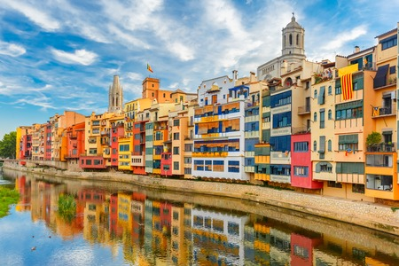 saint mary: Colorful yellow and orange houses and famous house Casa Maso reflected in water river Onyar, in Girona, Catalonia, Spain. Church of Sant Feliu and Saint Mary Cathedral at background.