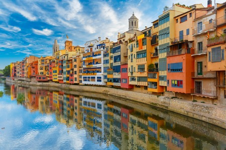 catalonia: Colorful yellow and orange houses and famous house Casa Maso reflected in water river Onyar, in Girona, Catalonia, Spain. Church of Sant Feliu and Saint Mary Cathedral at background.