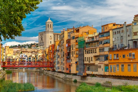 saint: Colorful yellow and orange houses and Eiffel Bridge, Old fish stalls, reflected in water river Onyar, in Girona, Catalonia, Spain. Saint Mary Cathedral at background.