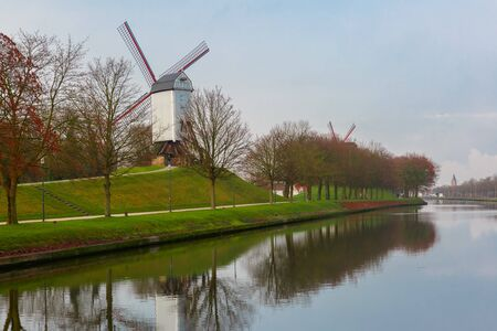 petrol powered: Picturesque rural landscape with Bonne Chiere Windmill and canal in Bruges, Belgium Stock Photo