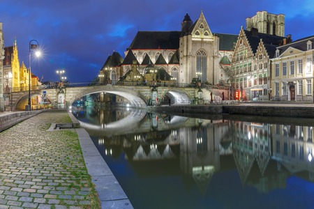 Quay Graslei, picturesque medieval St Michaels Bridge and church at night in Ghent, Belgium Stock Photo