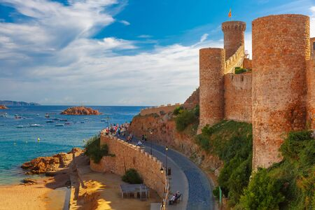 Round tower with the flag of Catalonia in fortress, Gran Platja beach and Badia de Tossa bay in Tossa de Mar on Costa Brava, Catalunya, Spain