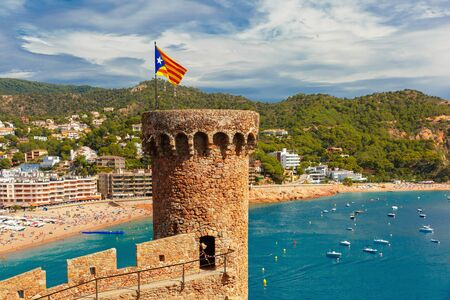 costa brava: Round tower with the flag of Catalonia in fortress, Gran Platja beach and Badia de Tossa bay in Tossa de Mar on Costa Brava, Catalunya, Spain