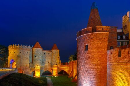 outpost: Semicircular fortified medieval outpost Barbican in the Old Town of Warsaw at night, Poland
