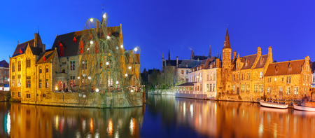 Scenic panorama with medieval fairytale town and tower Belfort from the quay Rosary, Rozenhoedkaai, at night, Bruges, Belgium Stock Photo
