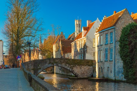 belfort: Scenic cityscape with a medieval tower Belfort, bridge and the Green canal, Groenerei, in Bruges in the morning, golden hour, Belgium