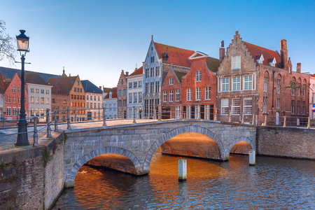 sunny cold days: Scenic city view of Bruges canal with beautiful medieval colored houses and sunny bridge in the morning, golden hour, Belgium Stock Photo