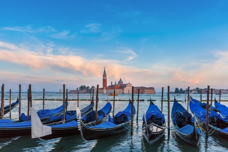 italia: Gondolas moored by Saint Mark square with San Giorgio di Maggiore church in the background in the evening, Venice, Italia