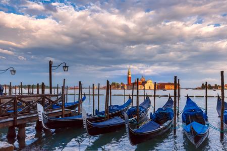 saint mark square: Gondolas moored by Saint Mark square with San Giorgio di Maggiore church in the background  during sunset, Venice, Italia