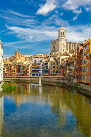 saint: Saint Mary Cathedral, colorful yellow and orange houses and famous white house Casa Maso reflected in water river Onyar, in Girona, Catalonia, Spain.