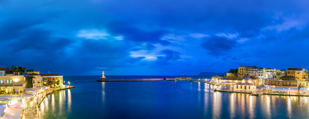 blue hour: Picturesque panoramic view of old harbour of Chania with Lighthouse and Kucuk Hasan Pasha Mosque during twilight blue hour, Crete, Greece Stock Photo