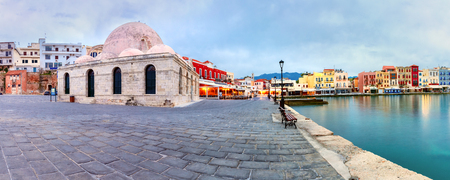 morning blue hour: Picturesque panoramic view of Venetian quay of Chania with Kucuk Hasan Pasha Mosque during cloudy morning blue hour, Crete, Greece