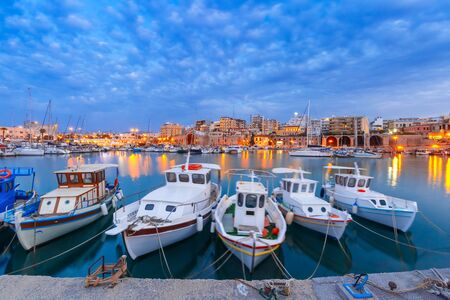 blue hour: Old harbour of Heraklion with fishing boats during twilight blue hour, Crete, Greece. Boats blurred motion on the foreground.