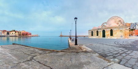 morning blue hour: Picturesque panoramic view of Venetian quay of Chania with Lighthouse and Kucuk Hasan Pasha Mosque during cloudy morning blue hour, Crete, Greece