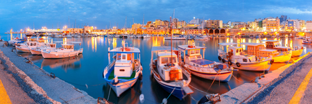 morning blue hour: Panorama of Old harbour with fishing boats during twilight blue hour, Heraklion, Crete, Greece. Boats blurred motion on the foreground. Stock Photo