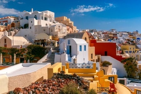 ia: Picturesque view of white houses, windmills and church with blue domes in Oia or Ia, island Santorini, Greece Stock Photo