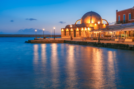 Picturesque view of Venetian quay of Chania with Kucuk Hasan Pasha Mosque during mornng blue hour before sunrise, Crete, Greece