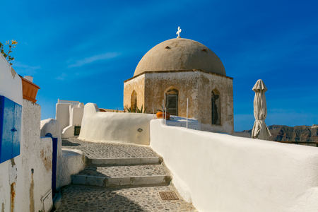 ia: Picturesque view of white houses and church in Oia or Ia, island Santorini, Greece
