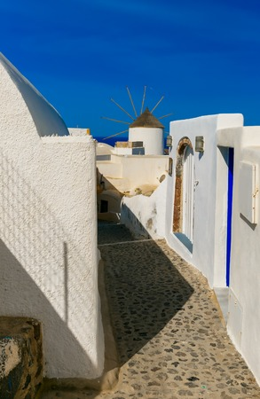 ia: Picturesque view of empty streer, white and blue houses and windmill in Oia or Ia, island Santorini, Greece Stock Photo