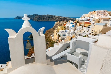 ia: Arch with a bell, white houses and church with blue domes in Oia or Ia, island Santorini, Greece Stock Photo