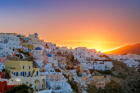 old houses: Old Town of Oia on the island Santorini, white houses and church with blue domes at sunrise, Greece