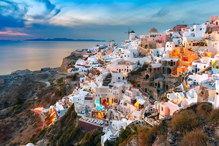 ia: Picturesque famous view, Old Town of Oia or Ia on the island Santorini, white houses and windmills at sunset, Greece