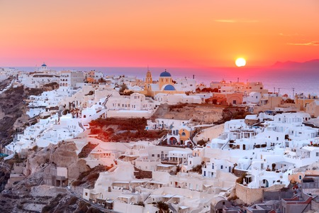 ia: Picturesque view, Old Town of Oia or Ia on the island Santorini, white houses and church with blue domes at sunset, Greece