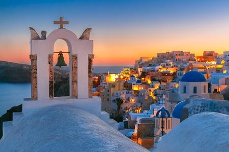Boog met een bel, witte huizen en de kerk met blauwe koepels in Oia of Ia bij zonsondergang, eiland Santorini, Griekenland Stockfoto