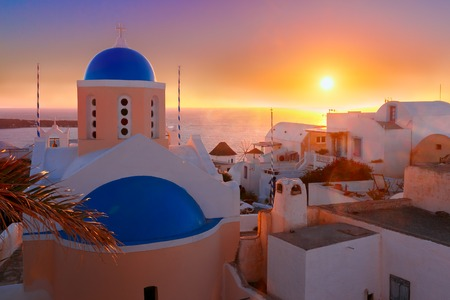 sea of houses: Picturesque view, Old Town of Oia or Ia on the island Santorini, white houses and church with blue domes at sunset, Greece