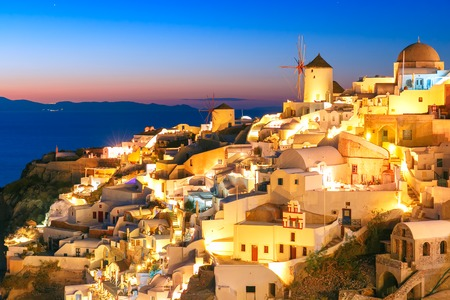 thera: Windmills in Oia on the island Santorini, white houses and church during twilight blue hour, Greece