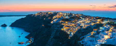 ia: Picturesque panorama, Old Town of Oia or Ia on the island Santorini, white houses, windmills and church with blue domes at sunset, Greece Stock Photo