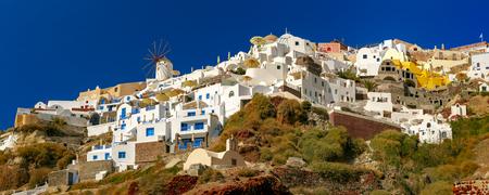 Panoramic view of windmills and white houses in Oia or Ia on the island Santorini, Greece Фото со стока