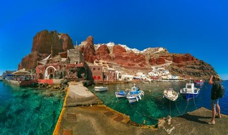 aegean sea: Photographer traveler takes pictures of Old port Amoudi of Oia village at Santorini island in Aegean sea, Greece Stock Photo