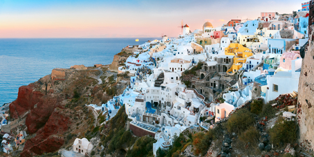 ia: Panoramic famous view, Old Town of Oia or Ia on the island Santorini, white houses and windmills at dawn, Greece Stock Photo