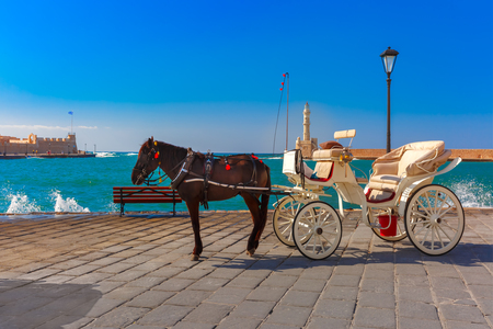 horse and carriage: Horse carriage and Lighthouse in old harbour of Chania on a summer sunny day, Crete, Greece